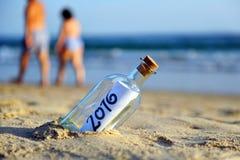 bouteille 2016 avec le message de nouvelle année, couple marchant sur la plage Photos stock