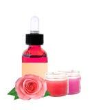 Bouteille avec le pétrole d'essence et les fleurs roses d'isolement sur le blanc Photographie stock libre de droits