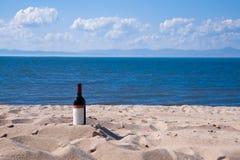 Bouteille avec le vin rouge sur la plage dans un jour ensoleillé d'été Nuages à sable jaune et blancs, ciel bleu et mer bleue dan Photographie stock