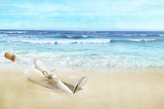 Bouteille avec un message sur la plage photographie stock