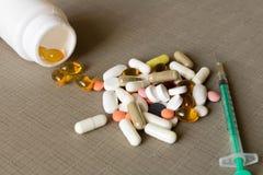 Bouteille blanche avec différentes pilules et seringue sur le fond gris image stock
