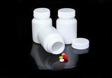 Bouteille blanche de médecine, pillules de couleur sur le noir. Image stock