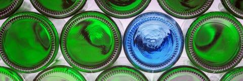 Bouteille bleue en verre parmi les bouteilles vertes Photo libre de droits