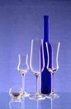 Bouteille bleue, trois verres à vin et un chandelier Image libre de droits