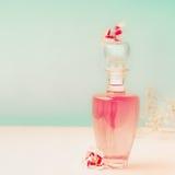 Bouteille cosmétique rose avec le produit de soin pour la peau ou le parfum avec des supports de fleurs sur la table au fond de t Photo libre de droits