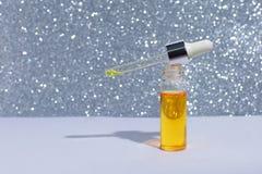 Bouteille cosm?tique ou m?dicale avec la pipette Produit liquide d'or dans la bouteille en verre avec le compte-gouttes Concept d images libres de droits