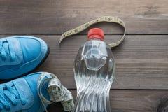 Bouteille d'eau, bande de règle et paires d'espadrilles Image libre de droits