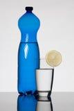 Bouteille d'eau bleue et verre remplis avec de l'eau images stock