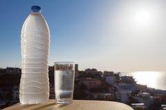 Bouteille d'eau complètement de l'eau avec des baisses et verre sur le fond de ville et de mer et le soleil Photo libre de droits