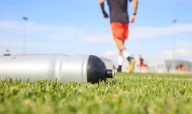 Bouteille d'eau du football du football sur le champ vert Images stock