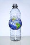 Bouteille d'eau en plastique avec la terre à l'intérieur Image stock
