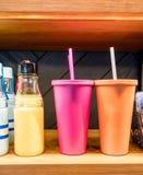 Bouteille d'eau en verre de poignée facile se tenant prêt le stainle rose et orange images stock