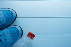 Bouteille d'eau et paires d'espadrilles la même couleur Image stock