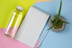 Bouteille d'eau, feuille vide de livre blanc et stylo sur un fond vibrant image libre de droits