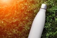Bouteille d'eau inoxydable de thermos, couleur blanche Maquette d'isolement sur le fond d'herbe verte avec l'effet de lumière du  image stock