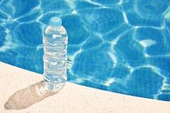 Bouteille d'eau par la piscine Photographie stock
