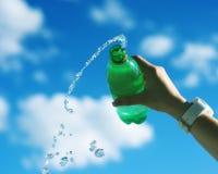 Bouteille d'eau pleuvante à torrents de main femelle Photographie stock