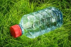 Bouteille d'eau sur l'herbe Photographie stock
