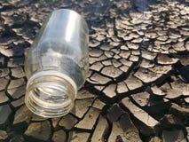 Bouteille d'eau sur la terre photographie stock