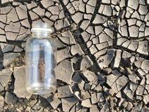 Bouteille d'eau sur la terre photos stock
