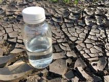 Bouteille d'eau sur la terre image stock