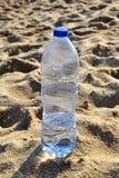 Bouteille d'eau sur le sable Image libre de droits
