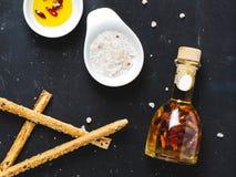 Bouteille d'huile avec des épices, bateau de sauce avec du sel rose photographie stock libre de droits