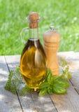 Bouteille d'huile d'olive, dispositif trembleur de poivre et herbes Images stock
