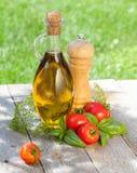 Bouteille d'huile d'olive, dispositif trembleur de poivre, tomates et herbes Photographie stock