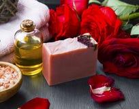 Bouteille d'huile de station thermale de Rose avec du savon naturel et les pétales de rose rouges Image libre de droits