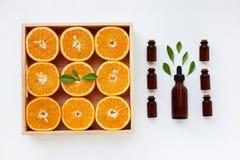 Bouteille d'huile essentielle des agrumes d'oranges avec l'ora frais photographie stock libre de droits