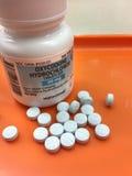 Bouteille d'Oxycodone sur le plateau de pharmacie avec des comprimés versés  Images stock