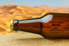 Bouteille de bière dans le désert Photographie stock libre de droits