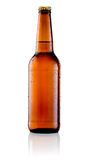 Bouteille de Brown de bière avec des baisses sur le fond blanc Photographie stock libre de droits