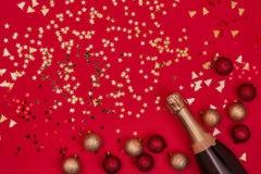 Bouteille de Champagne avec des ornements de Noël sur le fond rouge cop photo libre de droits