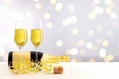 bouteille de champagne avec les verres remplis devant un fond d'or de bokeh image stock