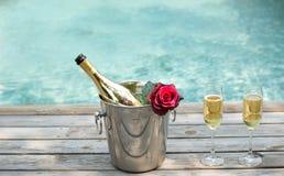 Bouteille de Champagne en seau à glace et verre de champagne en nageant p Photo stock