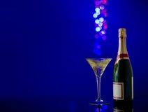 Bouteille de champagne et de verre sur le fond bleu Image libre de droits