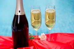 Bouteille de Champagne et verre de champagne avec la nappe rouge Images stock