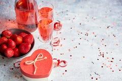 Bouteille de champagne rose, de verres avec les fraises fraîches et de cadeau en forme de coeur photo stock