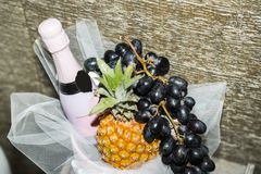 Bouteille de champagne de scintillement rose dans le panier avec des fruits Photo libre de droits