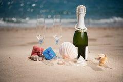 Bouteille de champagne sur la plage avec boîte-cadeau et coquilles Photographie stock libre de droits