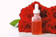 Bouteille de compte-gouttes avec des roses photographie stock libre de droits