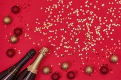 Bouteille de deux Champagne avec des ornements de Noël sur le fond rouge image libre de droits