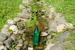 Bouteille de l'eau dans un ruisseau photo stock