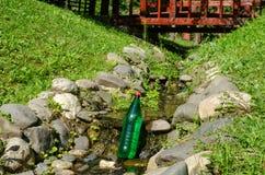 Bouteille de l'eau dans un ruisseau photos stock
