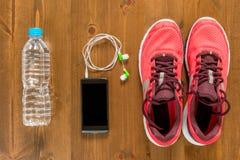 Bouteille de l'eau, de téléphone et de chaussures de course pour des sports Photographie stock libre de droits