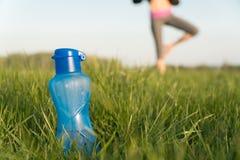 Bouteille de l'eau de sports la bouteille se tient sur l'herbe Mode de vie sportif Perte de poids images stock