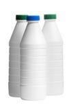 Bouteille de lait avec capuchons colorés d'isolement Photos libres de droits