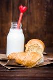 Bouteille de lait avec le coeur et le croissant sur le bois Images libres de droits